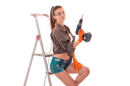 a young girl stands near the stairs and holding a drill to repair isolated on white