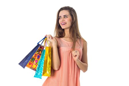 the girl looks to the side and holds the colorful packages from stores isolated on white