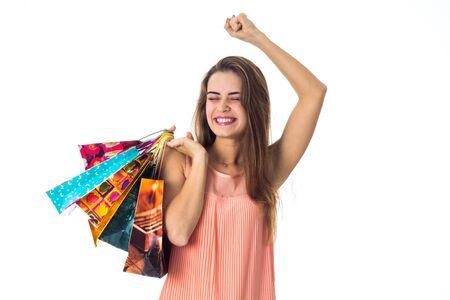 happy girl keeps a lot of large packages and lifted her arm up isolated on white