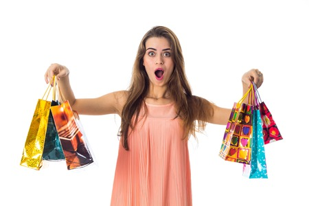 a young girl with a huge surprise holds the sides bright bags with giveaways is isolated on a white Reklamní fotografie