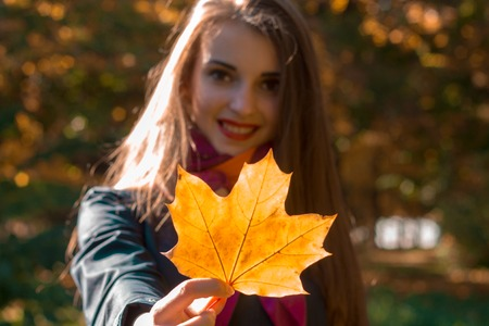girl stretched straight maple leaf and smiling close-up Stock Photo