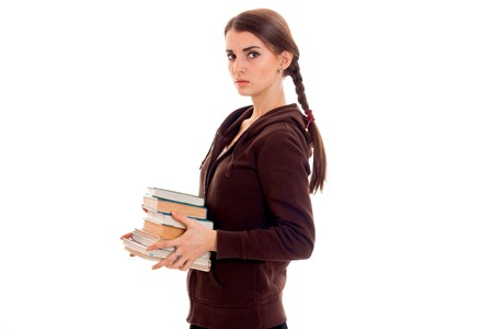 young girl with thoughtful person stands sideways and holding books isolated on white background Stock Photo