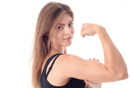 Sports girl shows muscle on hand closeup in studio Stock Photo
