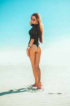 slim sexual brunette in black full body bikini and sunglasses posing on white sand
