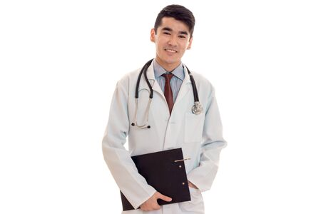 young cheerful brunette man doctor in uniform with stethoscope on his shoulders smiling isolated on white Stock Photo