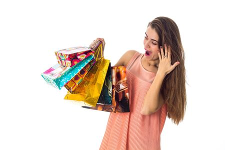 surprised girl looking at bright beautiful packages in hand isolated on white