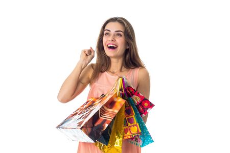 fun girl holding colorful packages with gifts is isolated on a white Stock Photo