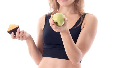 girl in black top shows Apple and cake closeup in studio