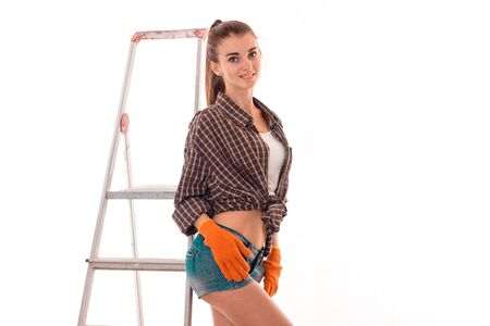 young cheerful brunette woman in uniform makes renovation with ladder looking at the camera and smiling isolated on white