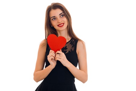happy brunette woman in love posing with red heart in her hands isolated on white Stock Photo