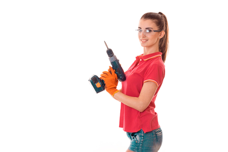 studio portrait of young sexy brunette girl in uniform and glasses makes renavation with drill in hands smiling on camera isolated on white