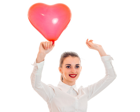 a cheerful young girl in white shirt lifted up a balloon in the shape of a heart is isolated on a white background