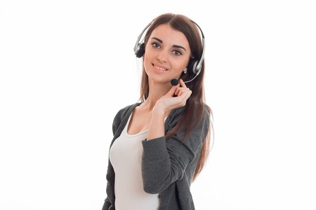 a young girl stands in the headphones with a microphone and looks into a camera isolated on white background Stock Photo