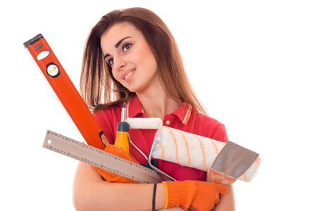young cheerful woman with dark hair in uniforl makes renovations with tools in her hands isolated on white