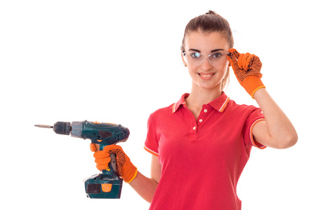 young happy woman with dark hair in uniforl makes renovations with drill in her hands isolated on white