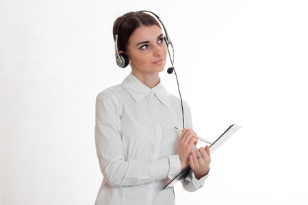 young girl in white shirt and headphones looks up and writes something in the Tablet is isolated on a white background