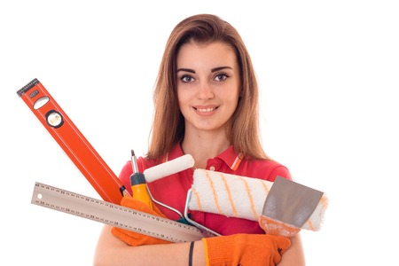 young beautiful girl looking into the camera, smiles and holds regular tools for the repairing of an isolated on white background