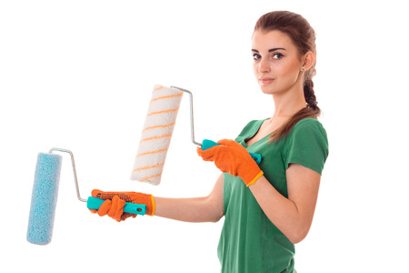 a young girl in the green shirt is worth turning sideways looks at the camera and holding rollers for painting isolated on white background