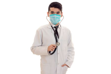 serious brunette male doctor in uniform with stethoscope on his neck and mask posing and looking at the camera isolated on white