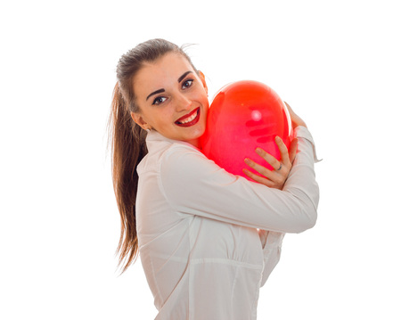 young smiling girl holding a large balloon in the shape of a heart is isolated on a white background