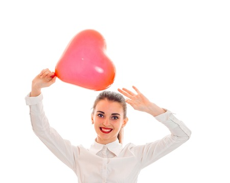 young smiling girl holding a large balloon in the shape of a heart and lifted her hands above her head isolated on white background