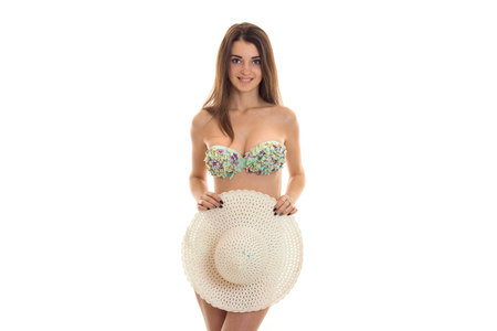 sexy young girl in a bathing suit with beautiful breasts holds Hat isolated on white background