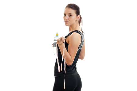 young beautiful sport girl stands with his back to the camera and keep the measuring tape and water isolated on white background