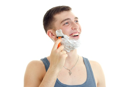 young gay guy with foam on his face looking sideways and shaves isolated on white background