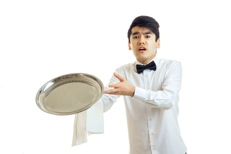 young guy waiter throws forward ware tray is isolated on a white background
