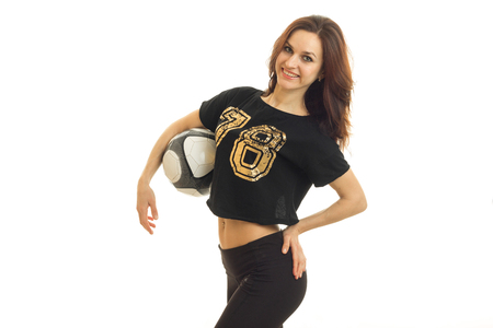 Pretty cheerful woman smiling on camera with soccer ball in her hands isolated on white background