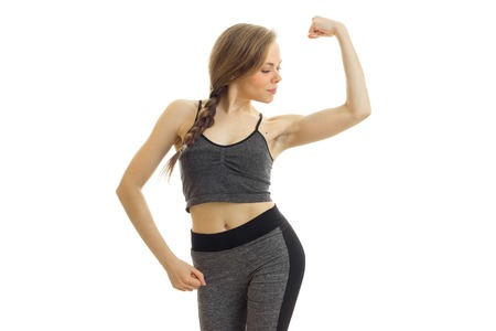 young fitness girl grey sports suit looks at the biceps on hand isolated on white background Stock Photo
