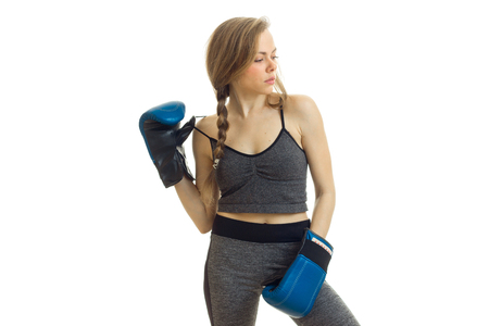 Slim young girl with pigtail stands in boxing gloves and looks toward isolated on white background