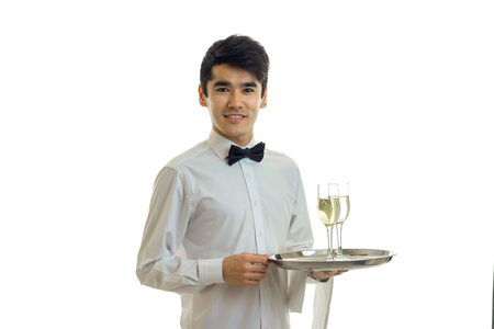 charming young waiter looks straight smiles and holds a tray with glasses isolated on white background Stock Photo