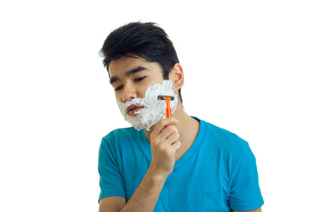young black haired guy lowered his head down and shaves his beard with a razor is isolated on a white background