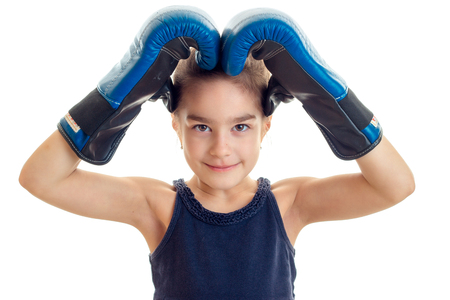pugilist: little girl holding hands over the head with a large boxing gloves close-up isolated on white background