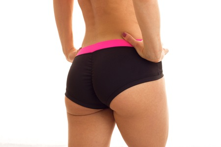 beautiful buttocks of a young girl in a black sports shorts close-up isolated on white background
