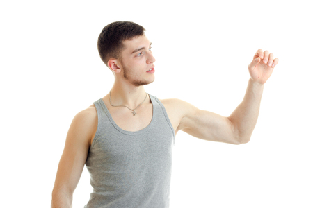 a young guy in the gray shirt looks toward raises his hand and straining muscles isolated on white background