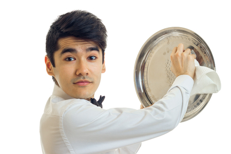 Portrait of a handsome young waiter that looks into the camera and side tray cloth close-up isolated on white background Stock Photo