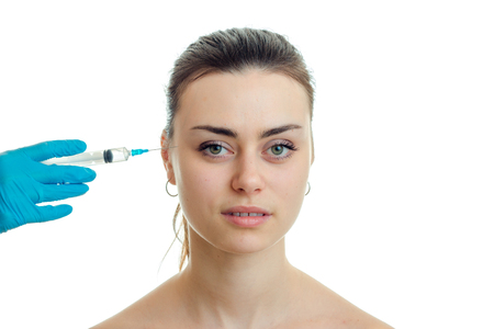 Portrait of young beautiful girls which receives an injection syringe on her face close-up isolated on white background
