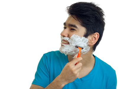 young gay guy turned his head to the side and shaves his beard with foam isolated on white background Stock Photo