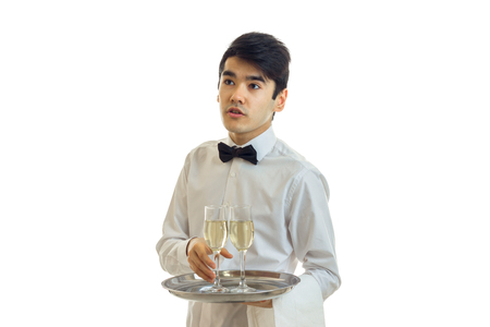 waistcoat: the young waiter looks away and takes the ball tray with a glass of champagne is isolated on a white background Stock Photo