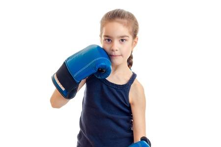 pugilist: little cute girl in boxing gloves looks at camera isolated on white background