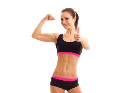 young smiling girl with press on her stomach in the sports top shows muscle on hand isolated on white background