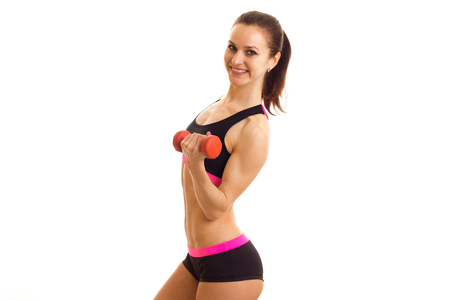 beautiful young fitness girl smiling and holding a small dumbbell isolated on white background