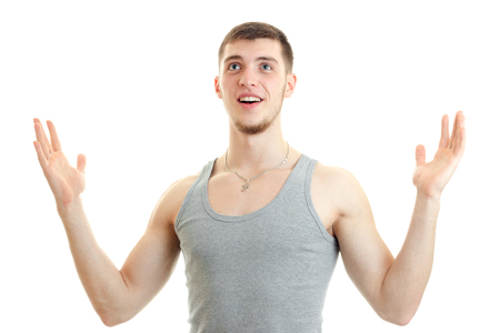 surprised young guy raised his hands, looking up and smiling isolated on white background Stock Photo