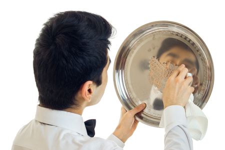 waxes: the young waiter with black hair waxes to shine tray for cupboards close-up isolated on white background Stock Photo