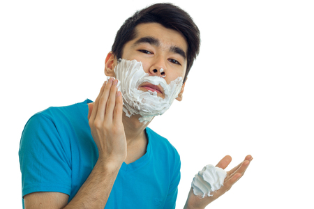 young black haired guy worth with foam on his face close-up isolated on white background Stock Photo