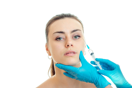 a young girl without makeup on the face receives an injection in blue gloves close-up isolated on white background