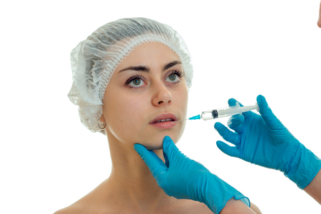 a young girl stands in the medical hair CAP and it receives an injection syringe on her face in gloves close-up isolated on white background. Stock Photo