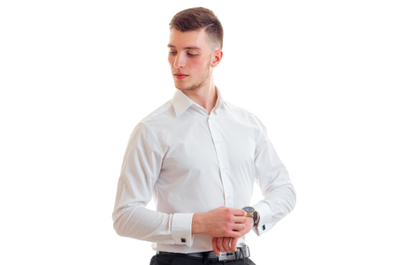 corrects: beautiful tall young guy in a white shirt corrects watches on hand isolated on white background